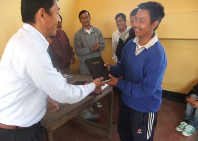 Director Mathotmi Handing out Bible to Student